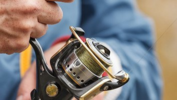 Fishing reel being held by an older person's hands